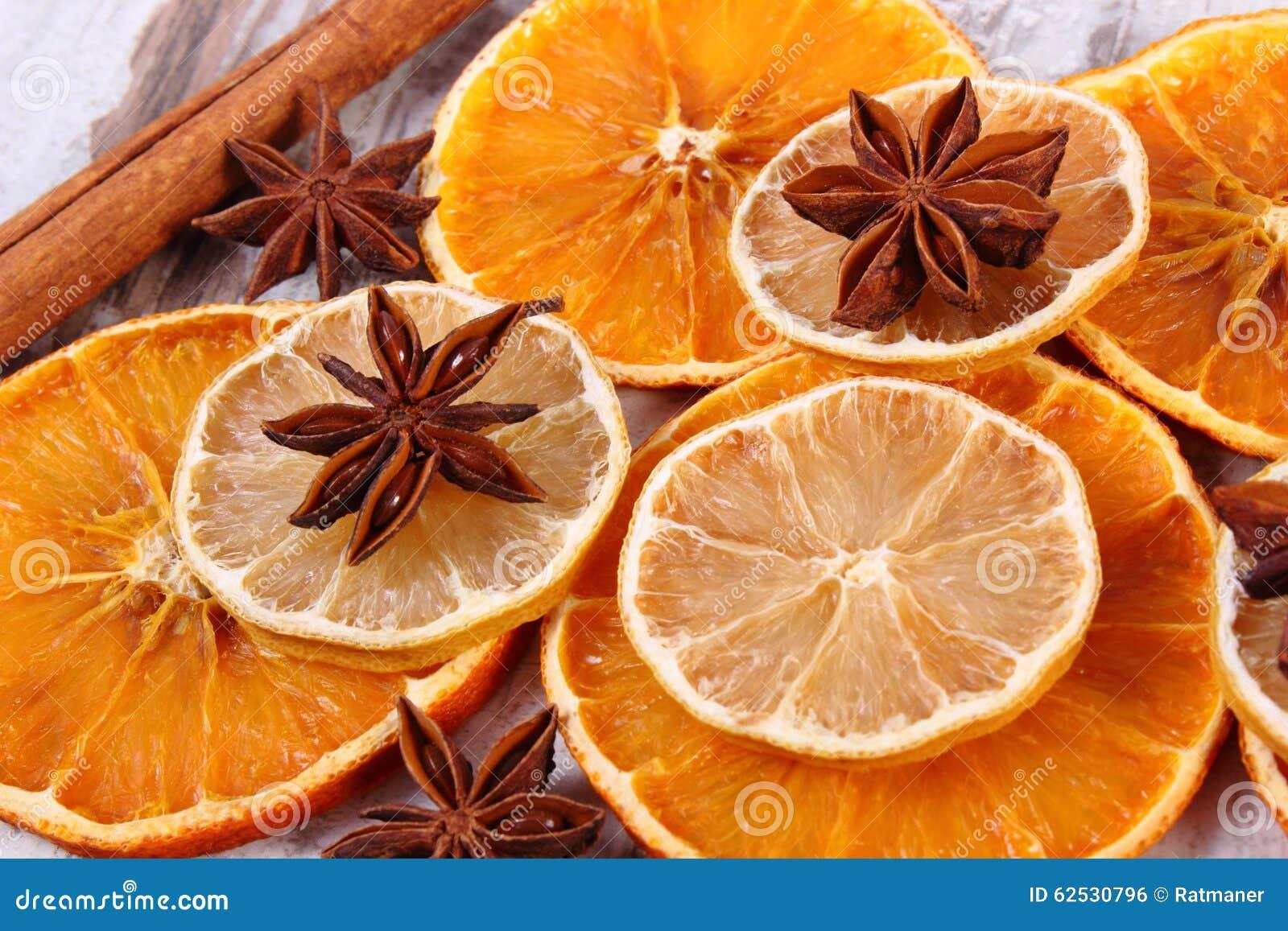 切片干柠檬、桔子和香料在老木背景