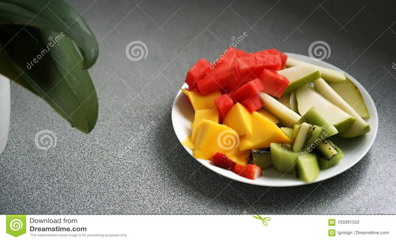 切的和切成小方块的异乎寻常的果子在一块板材在背景中服务,有一棵植物的