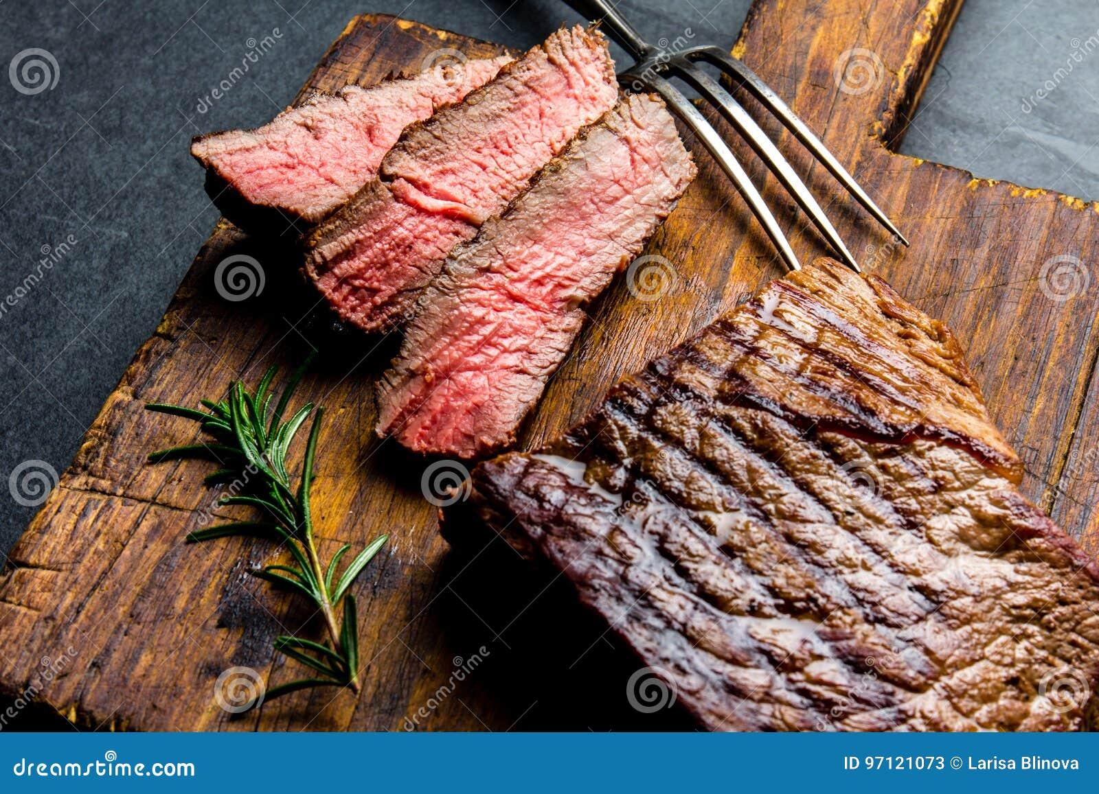 切的烤半生半熟牛排在木板烤肉, bbq肉牛里脊肉服务 顶视图,板岩背景