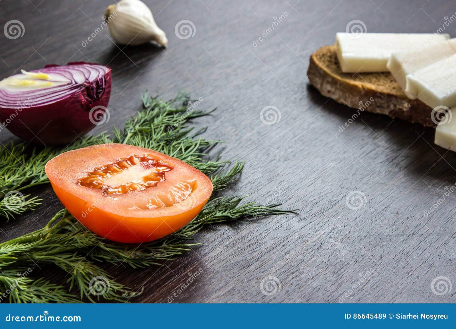 切红洋葱、蕃茄、莳萝、猪油salo和大蒜在木桌上