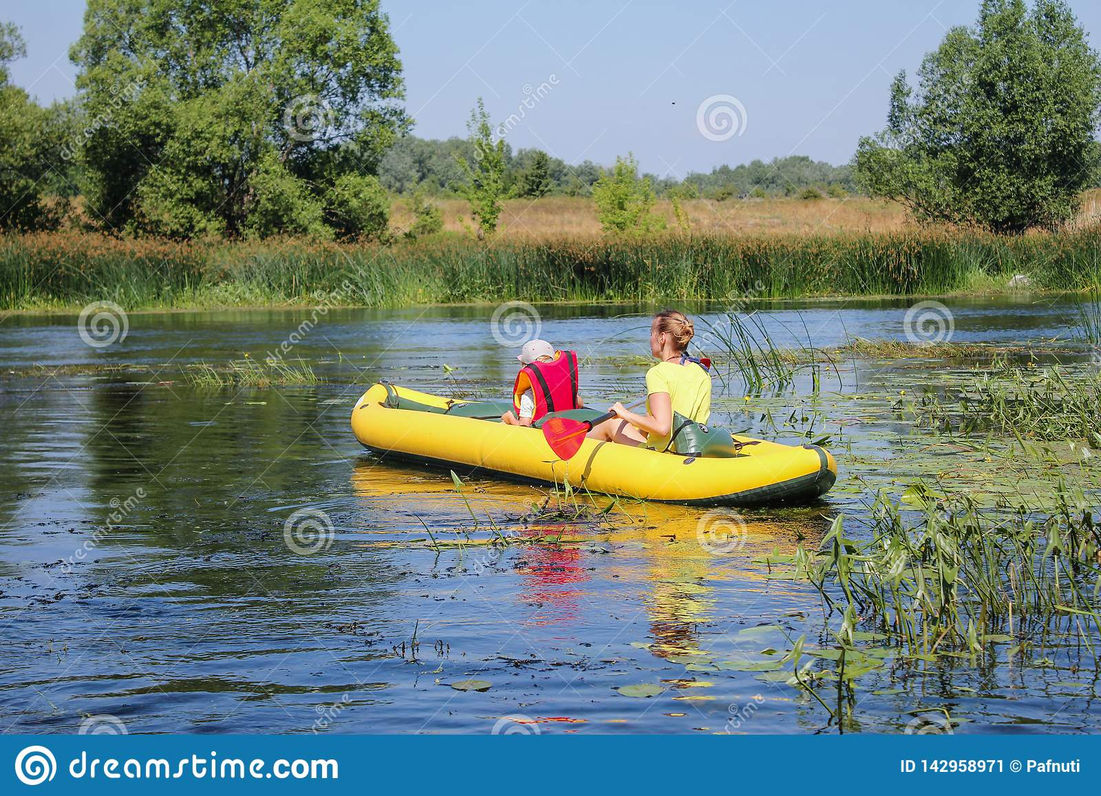 划皮船在河的家庭 有他的mothe的小男孩