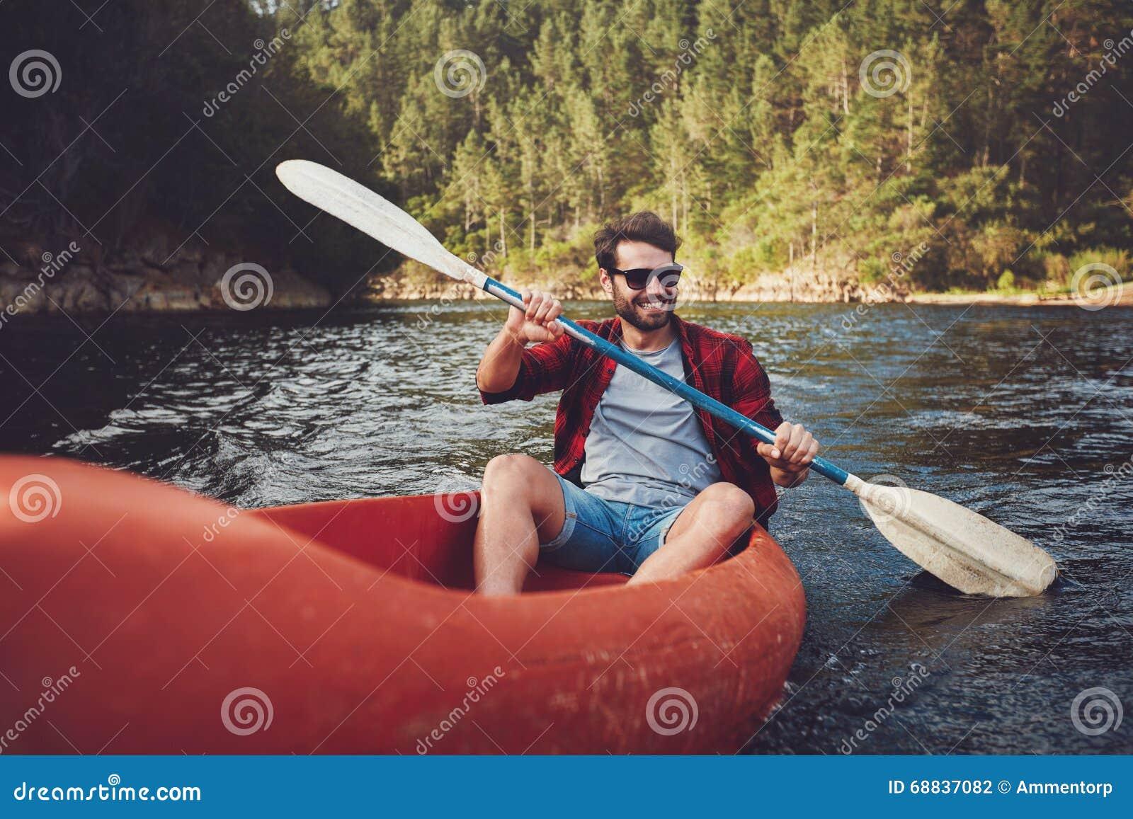 划皮船在湖的年轻人