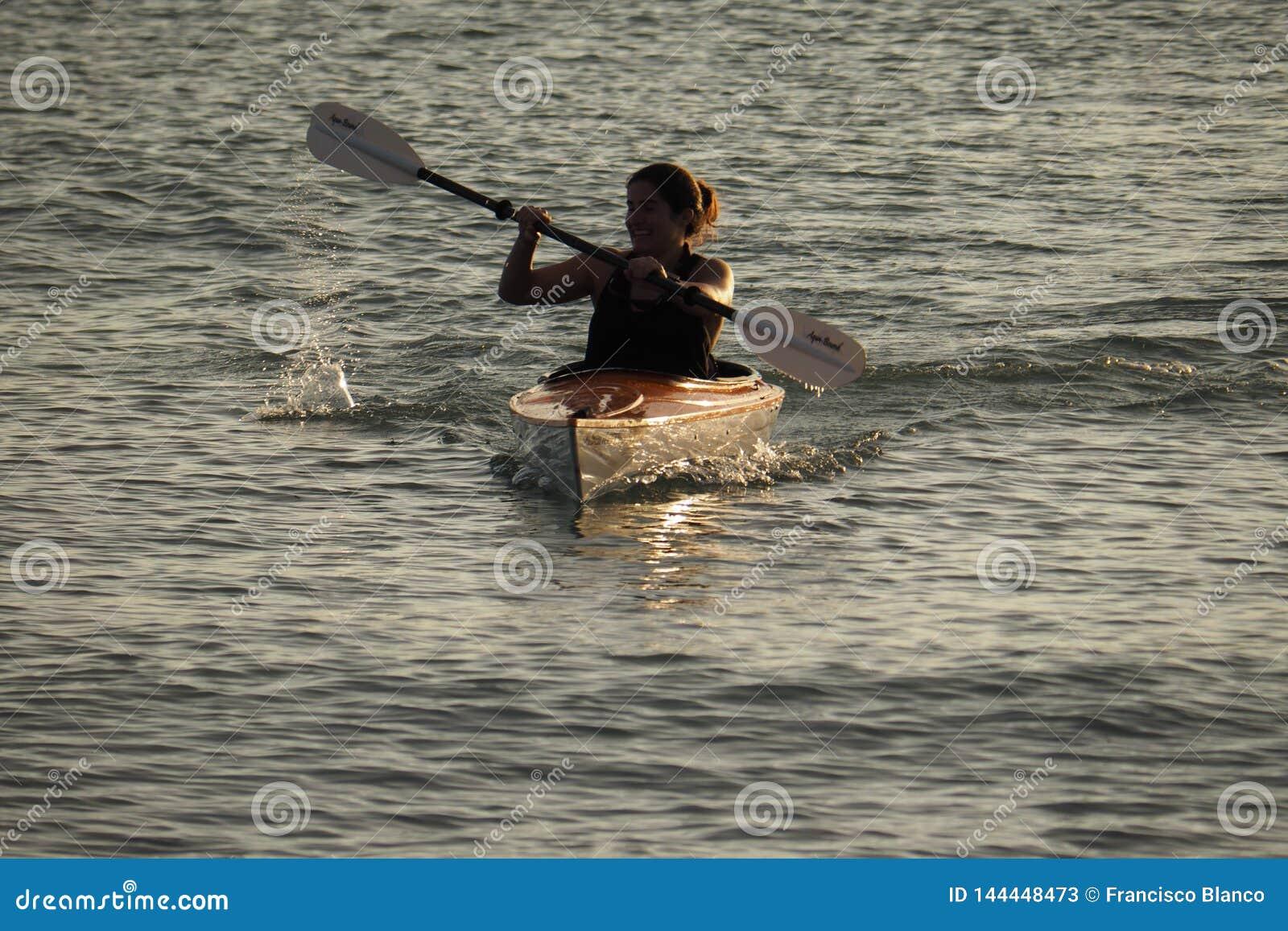 划皮船Captiva海岛的年轻女人在日落