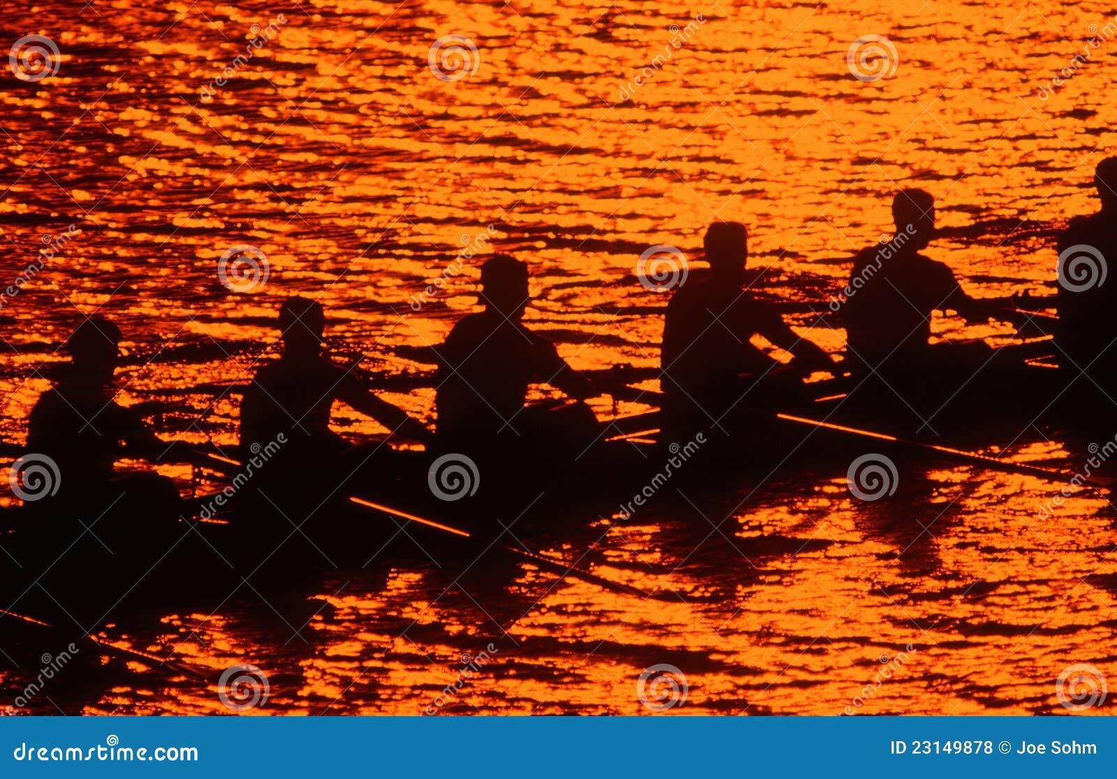 划船乘员组剪影在日落的