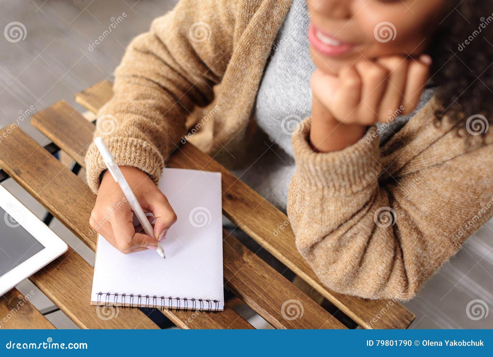 创造性女孩采取在笔记薄的笔记