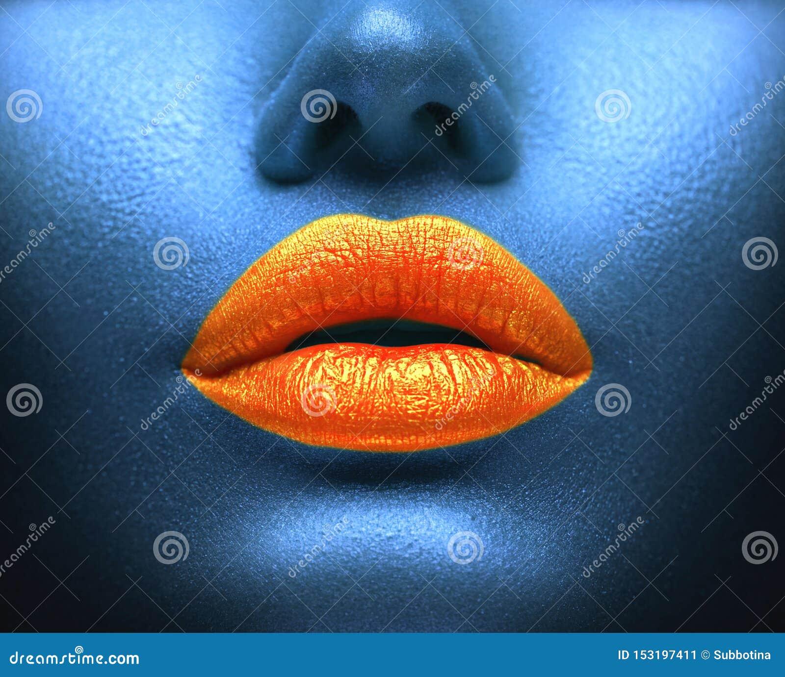 创造性的五颜六色的构成 Bodyart,在性感的嘴唇,女孩的lipgloss装腔作势地说 在蓝色皮肤的橙色嘴唇