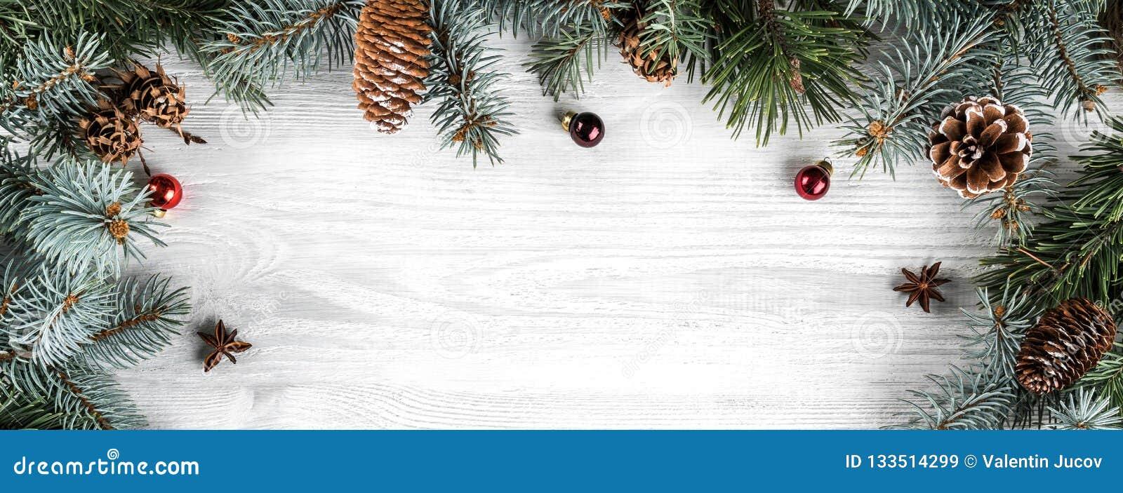创造性的框架由圣诞节冷杉分支做成在与红色装饰的白色木背景