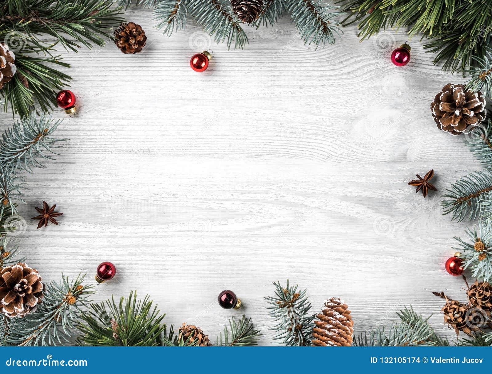 创造性的框架由圣诞节冷杉分支做成在与红色装饰,杉木锥体的白色木背景 Xmas和新年题材