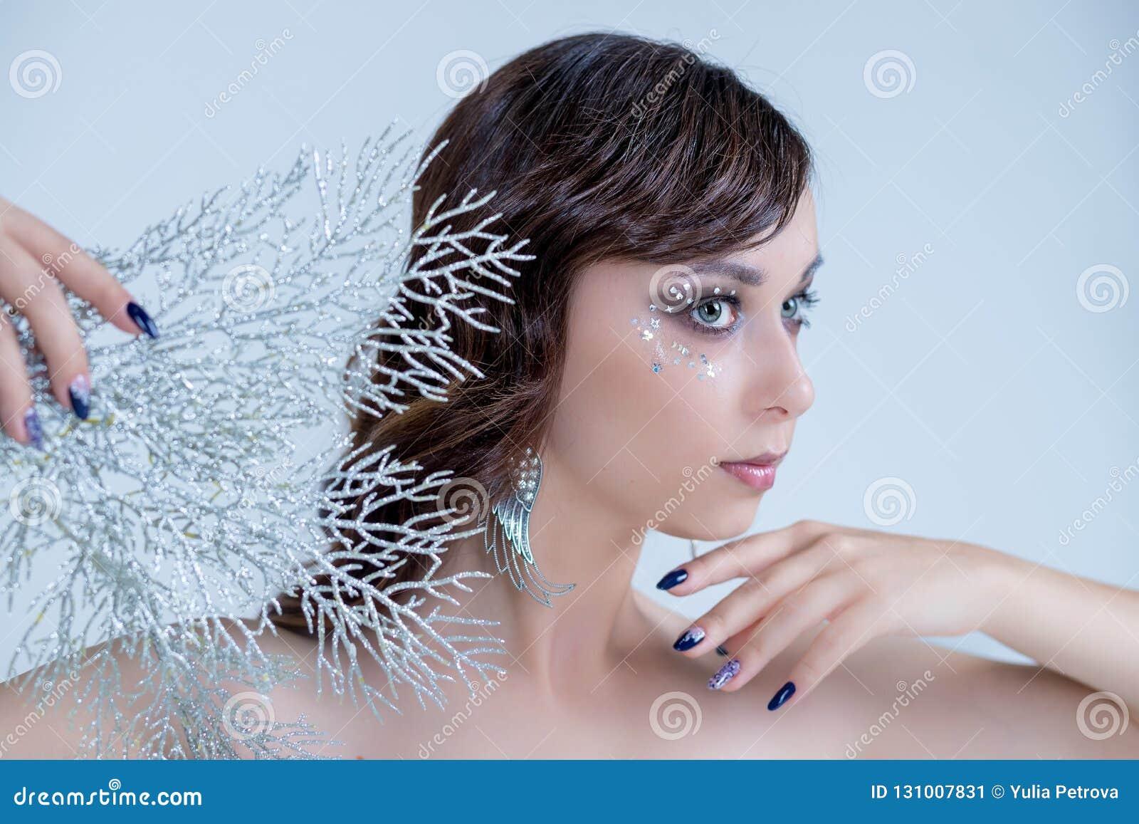 创造性的银色艺术性的构成的年轻女人 神仙的冰女王/王后典雅的姿势,银色和白色分支,不可思议的冬天