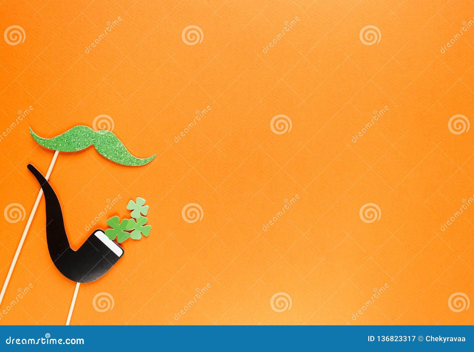 创造性的st帕特里克斯天橙色背景 爱尔兰假日庆祝的平的被放置的构成与照片摊装饰的:帽子,玻璃