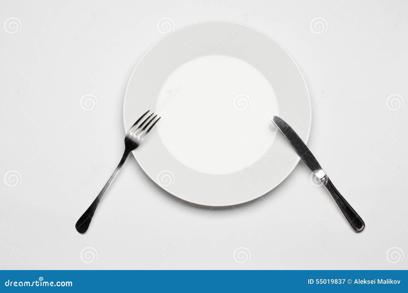 利器和餐馆题目:说谎在一张白色桌上的叉子刀子和白色板材隔绝在演播室顶视图
