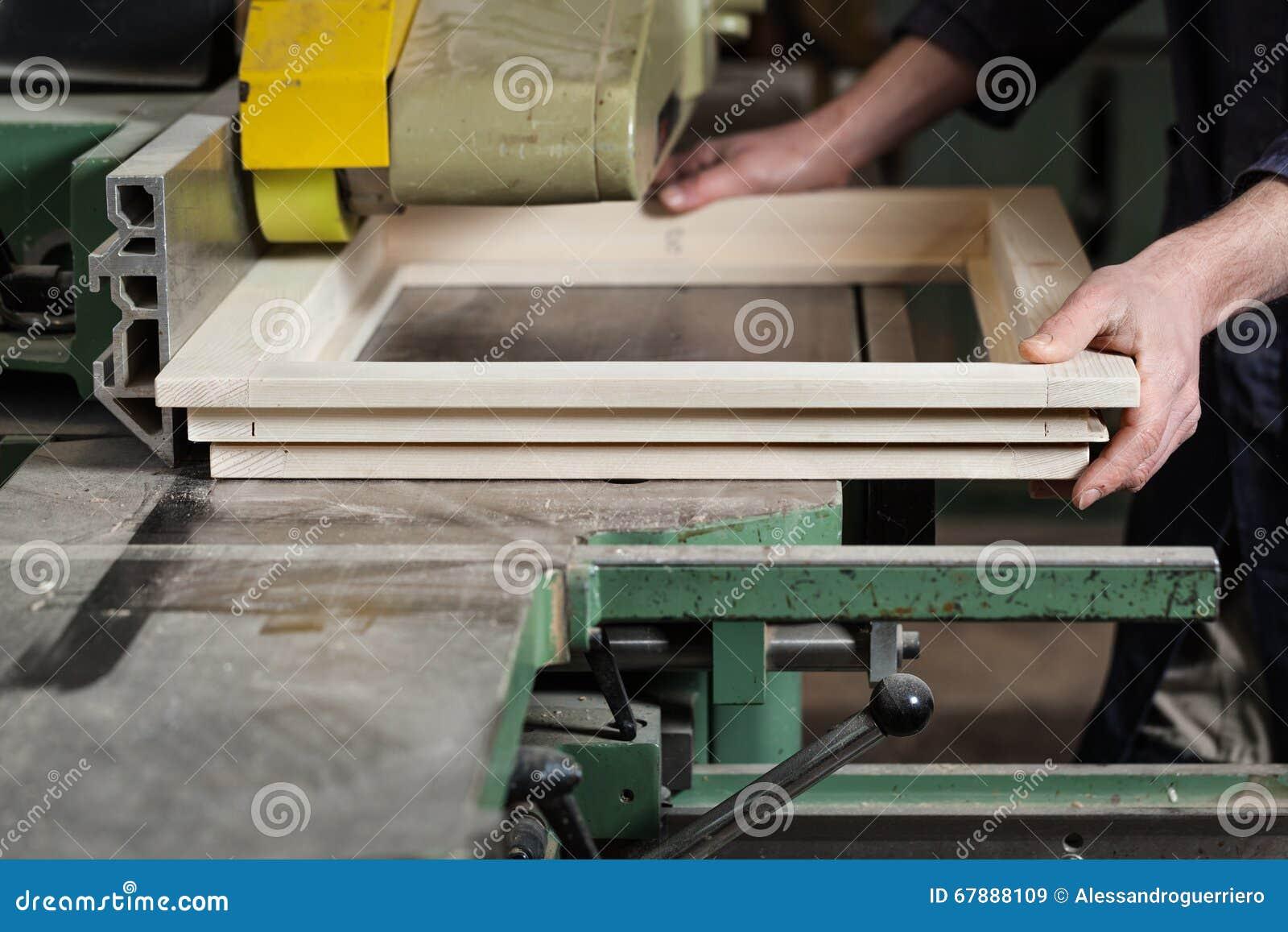 削减木窗架的木匠的手