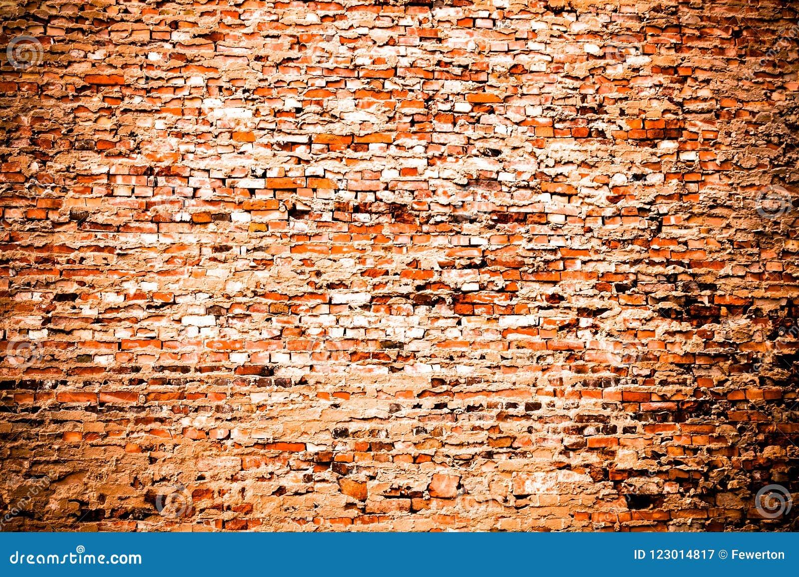 剩余水泥和灰色油漆部分盖的老和被风化的脏的红色橙色砖墙当纹理背景用轻微vi