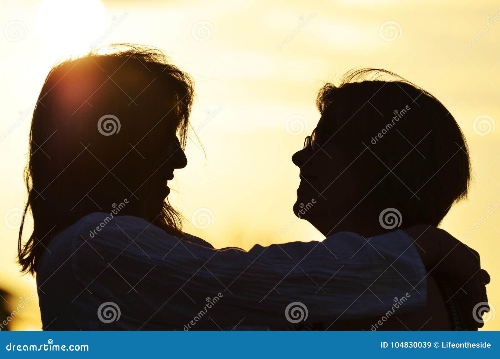 剪影拥抱母亲的女儿,笑,一起爱