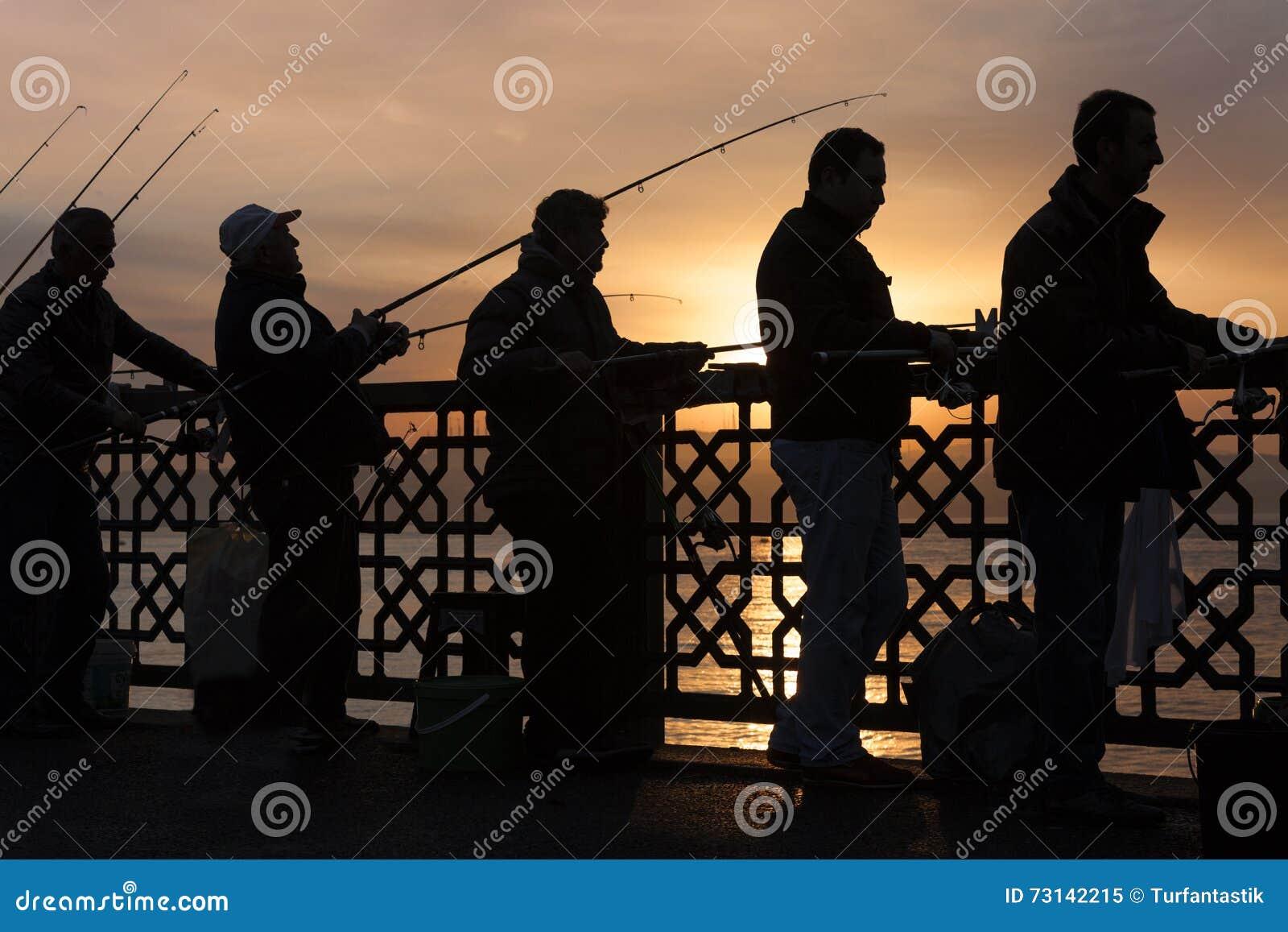 剪影的渔夫在日出,在加拉塔桥梁,在伊斯坦布尔,土耳其