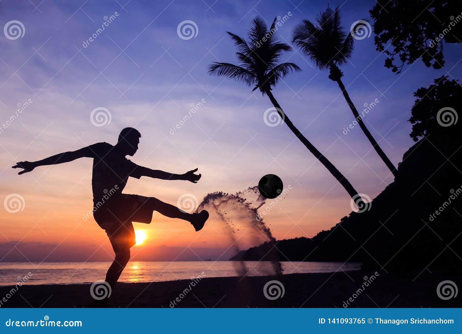 剪影齐射在海滩的反撞力橄榄球,在日出的亚洲人戏剧足球