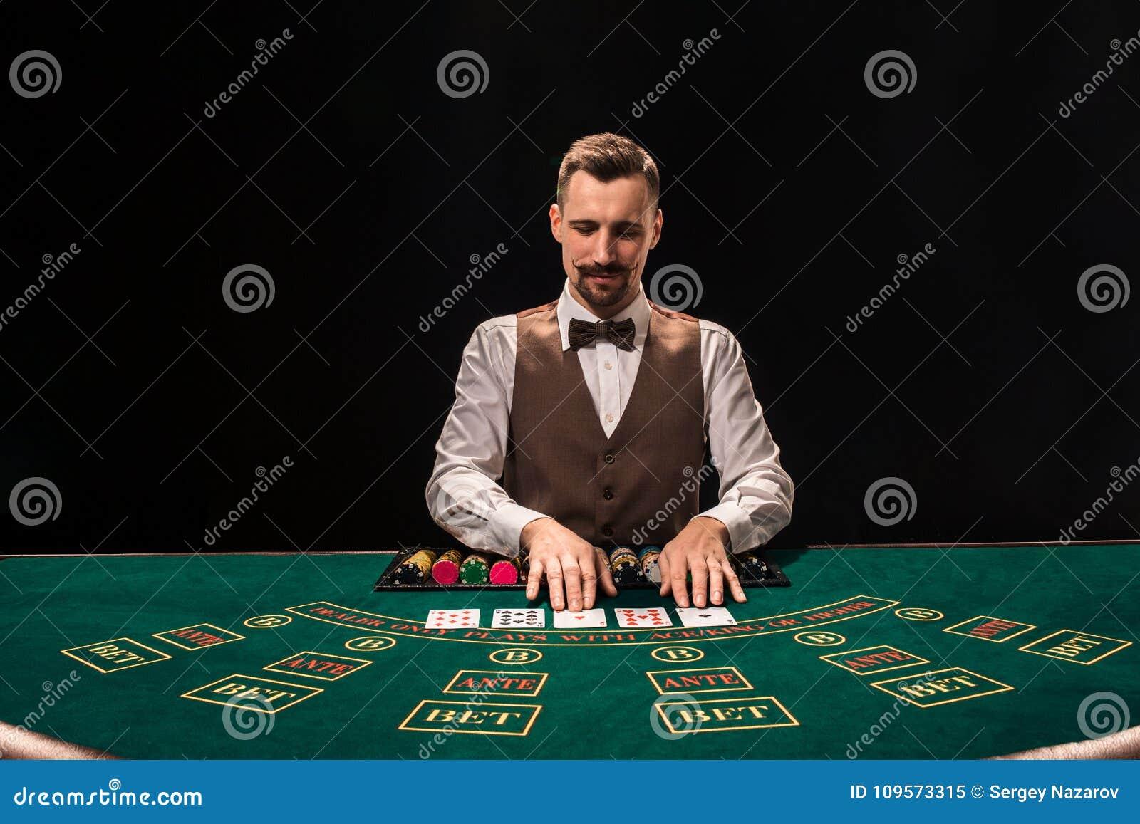 副主持人的画象在桌上拿着纸牌,赌博切削 黑色背景