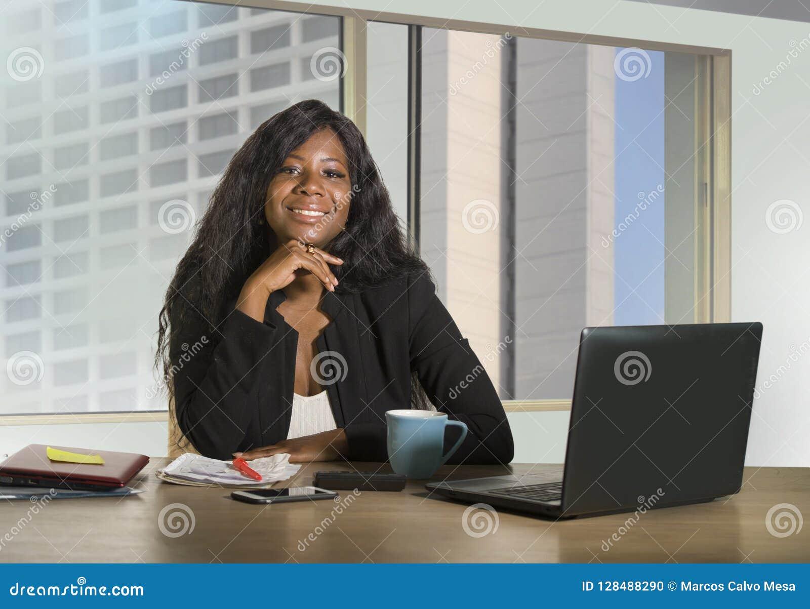 办公室公司画象年轻愉快和有吸引力黑非裔美国人女实业家工作确信在计算机书桌sm