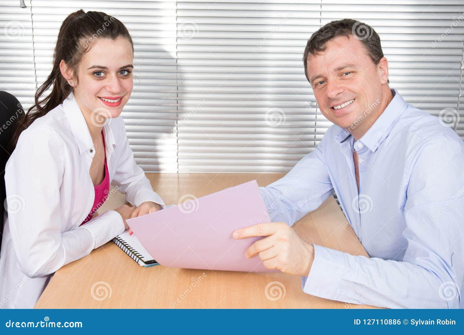 办公室同事一起看一个运作的文件夹办公桌