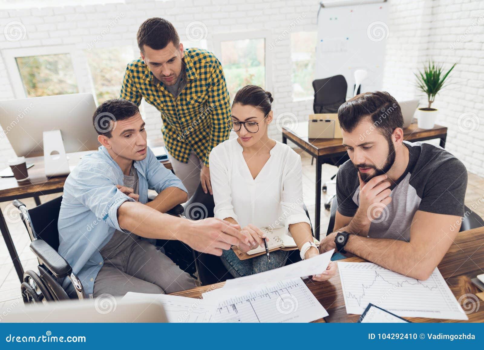 办公室工作者和一个人轮椅的谈论工作事态 他们在一个明亮的办公室运作