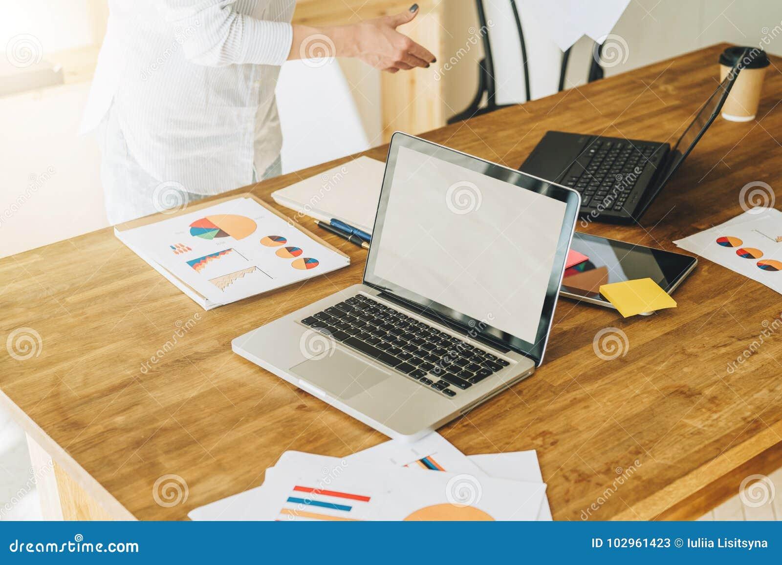 办公室,书桌 一台膝上型计算机的特写镜头在一张木桌上的 附近纸图表,图,图,一种数字式片剂