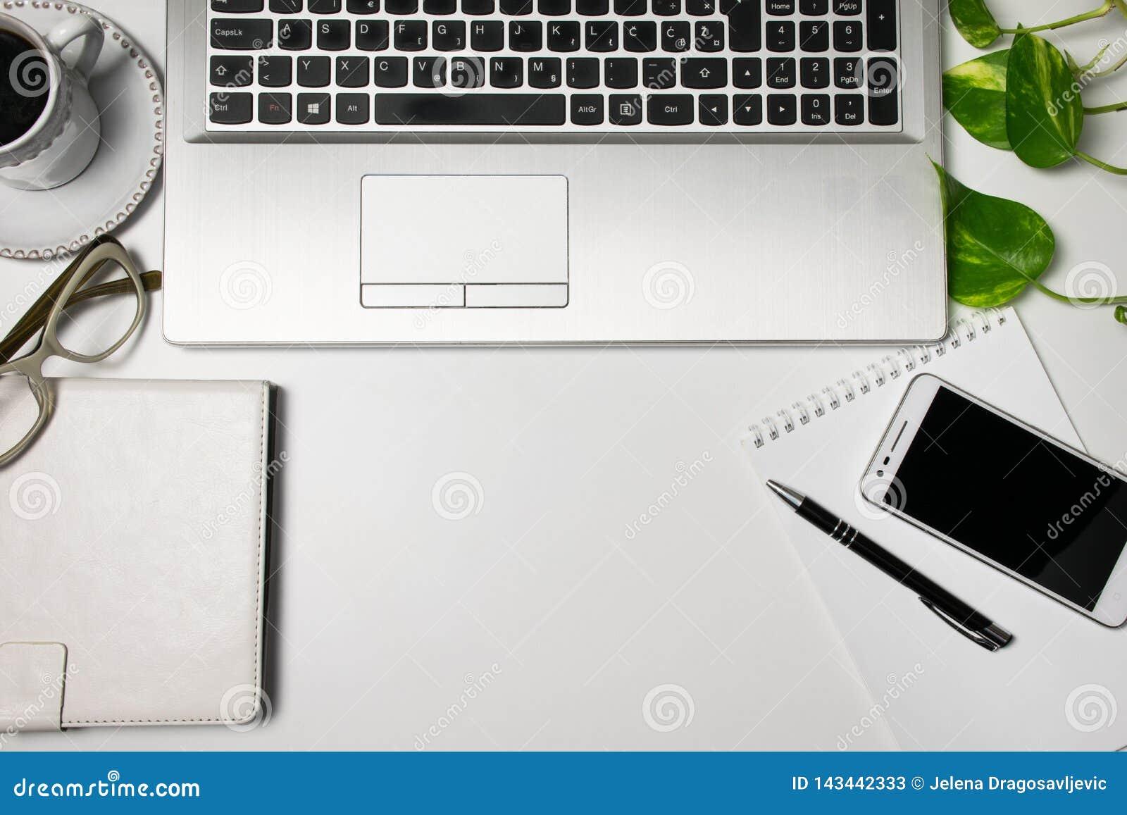 办公桌台式视图和供应,膝上型计算机,杯子无奶咖啡,玻璃,植物,在白色背景的手机