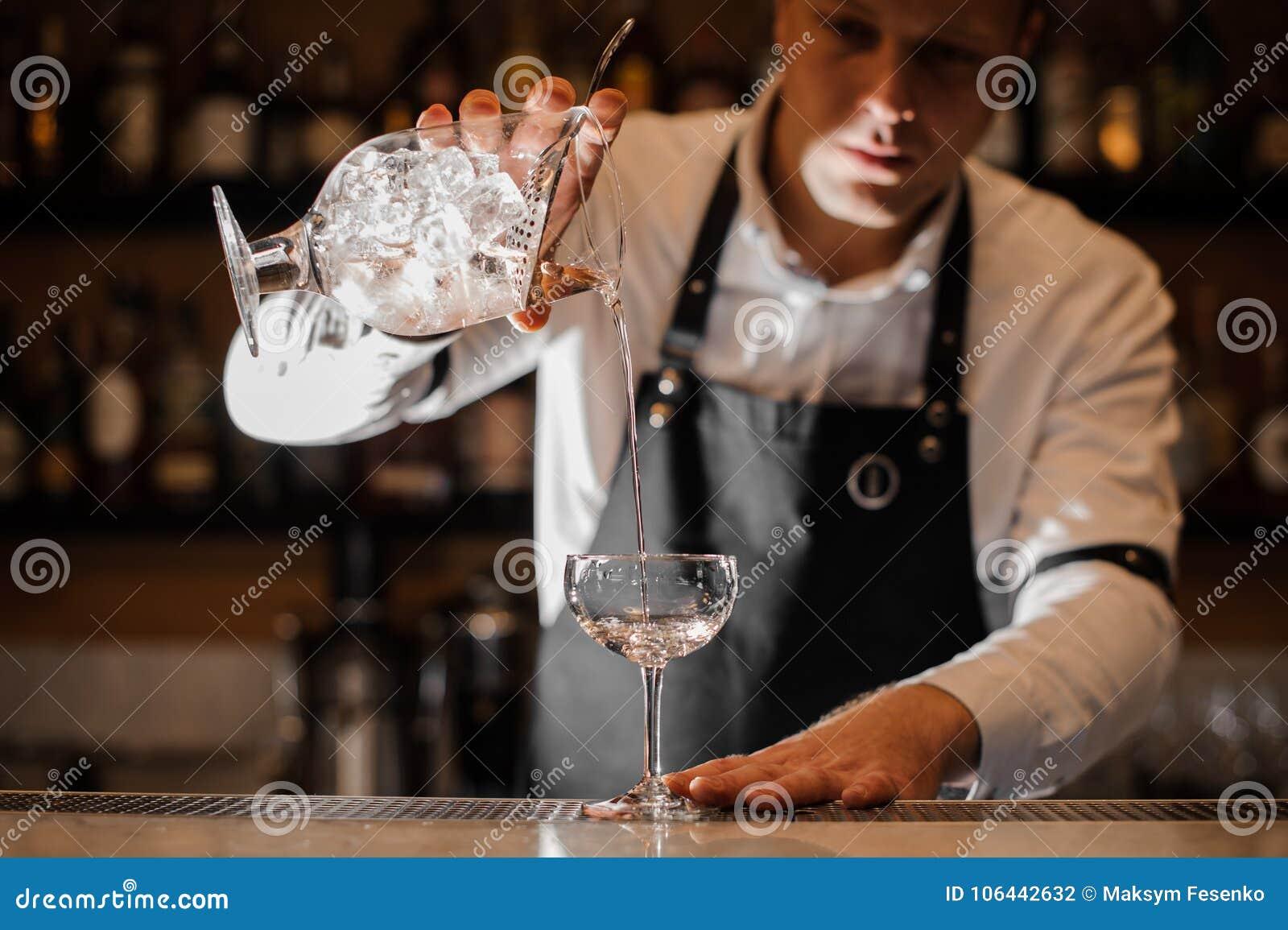 加伏特加酒的男服务员入在黑暗的光的一个鸡尾酒杯
