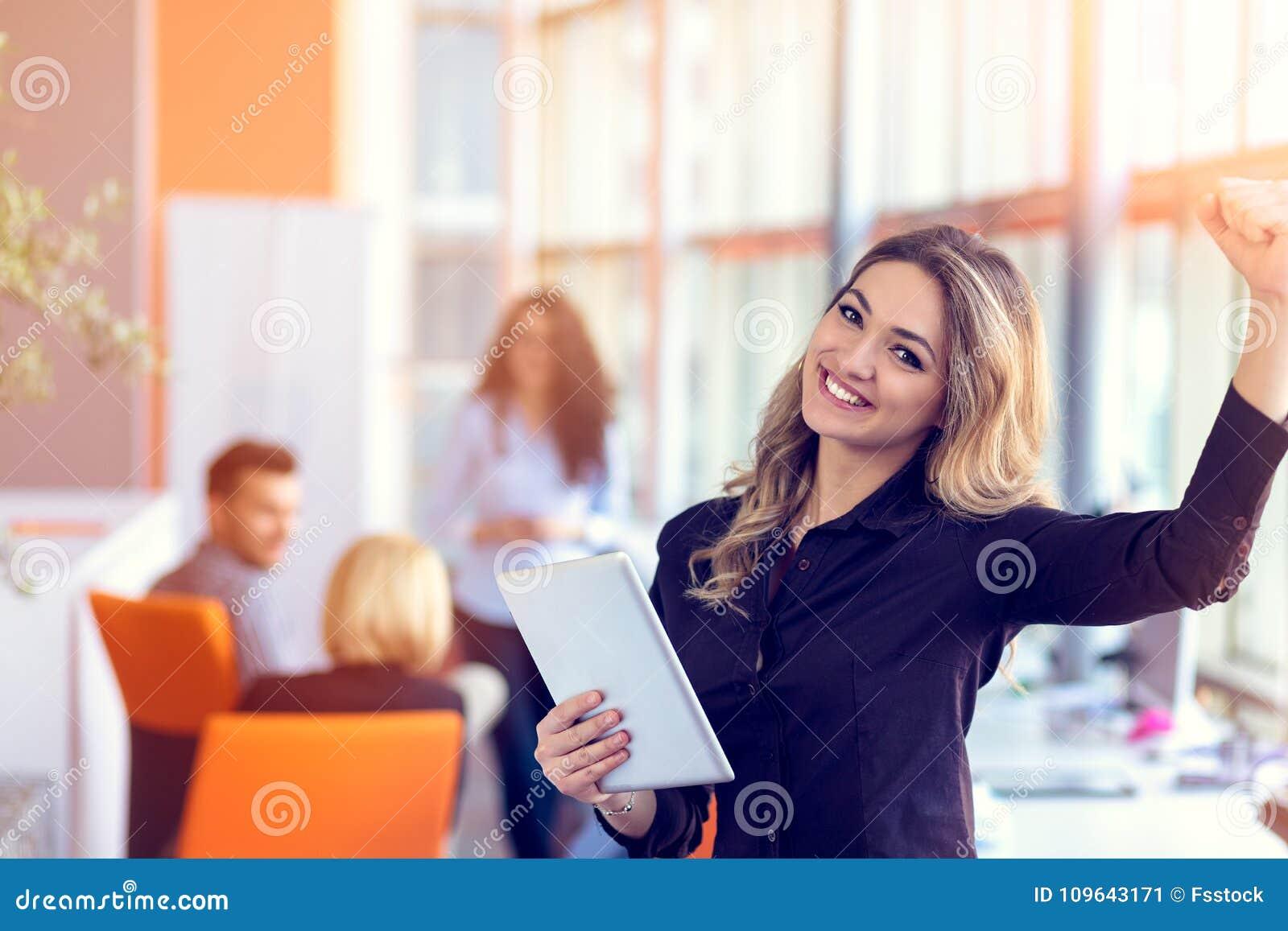 加入一个数字时代 拿着数字式片剂的快乐的少妇,当他的工作在背景时的朋友