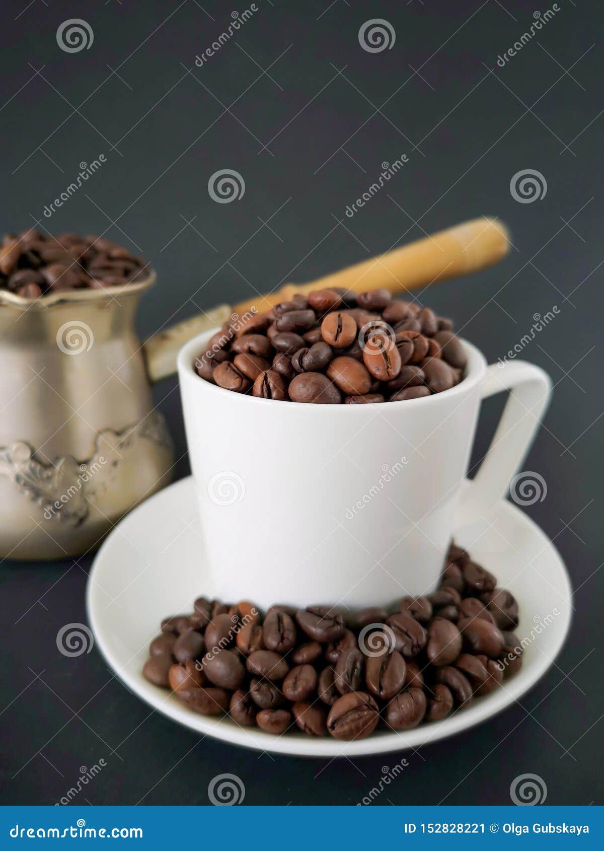 加奶咖啡茶杯;在桌上驱散的咖啡豆 在背景中是cezve 黑背景
