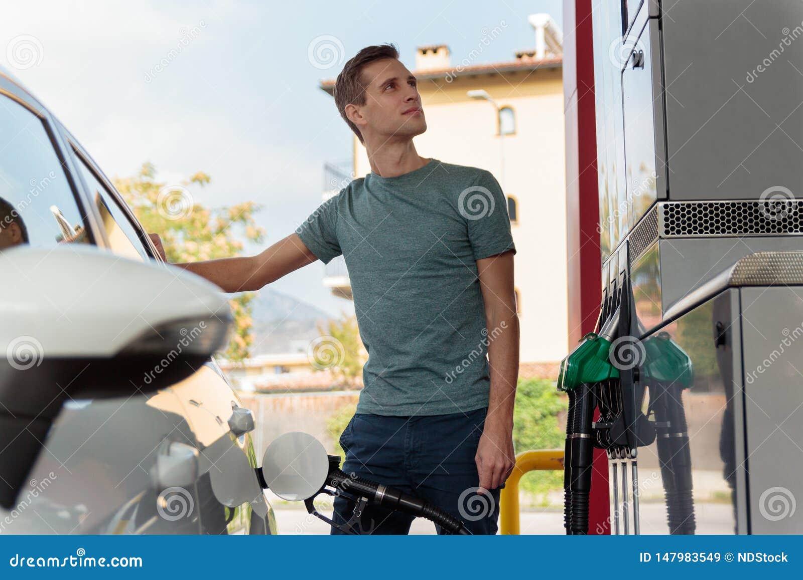 加油汽车的英俊的年轻人在一好日子