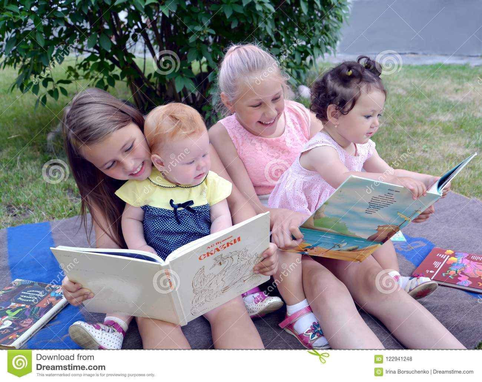 加里宁格勒,俄国 另外年龄的孩子充满热情的在庭院里考虑书,坐一棵草
