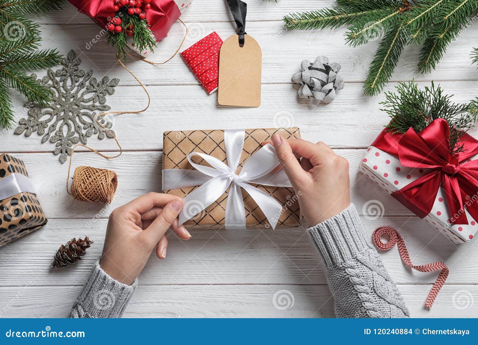 包裹圣诞节礼物的妇女在木桌上