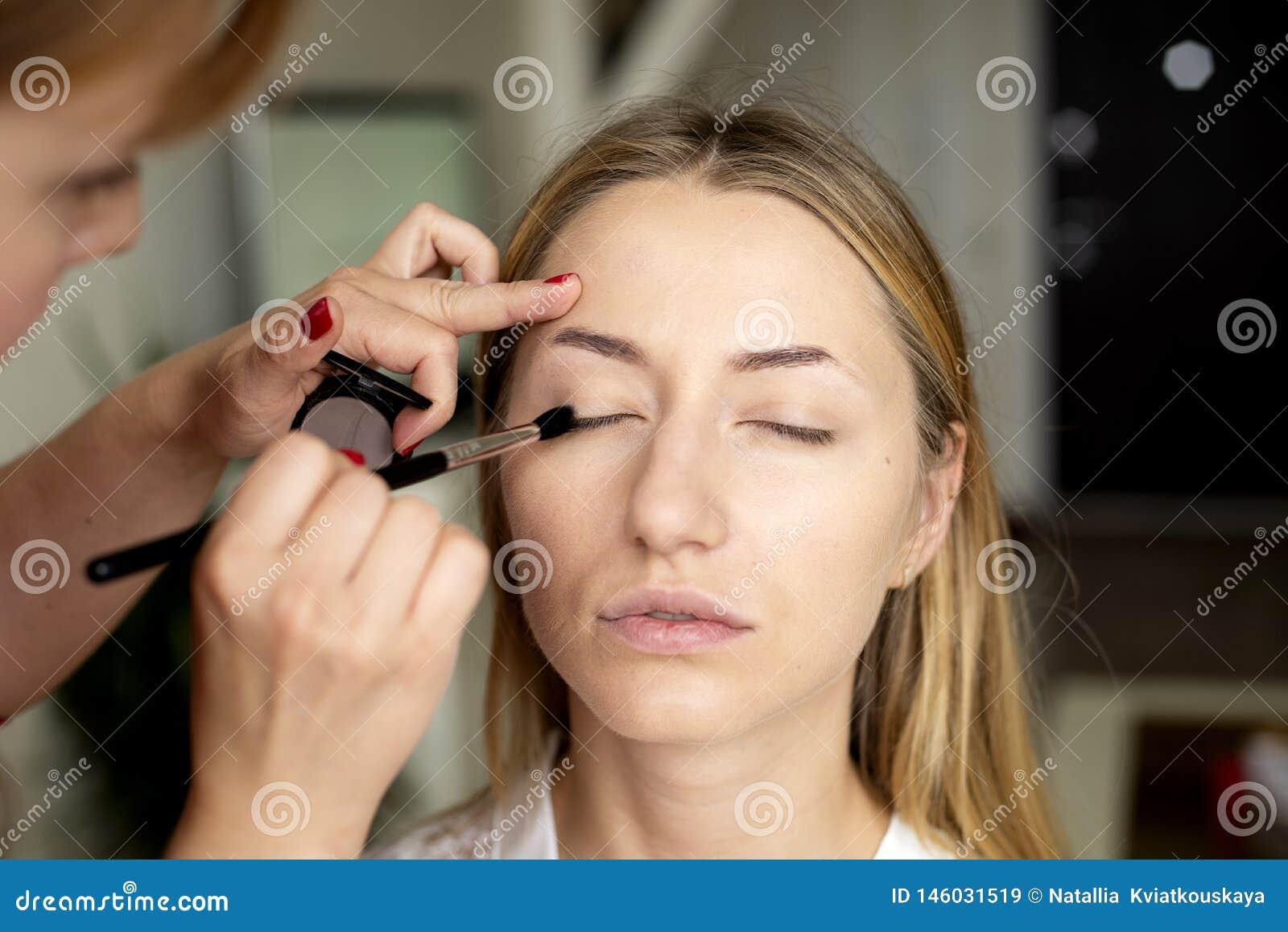 化妆师在女孩的面孔投入构成