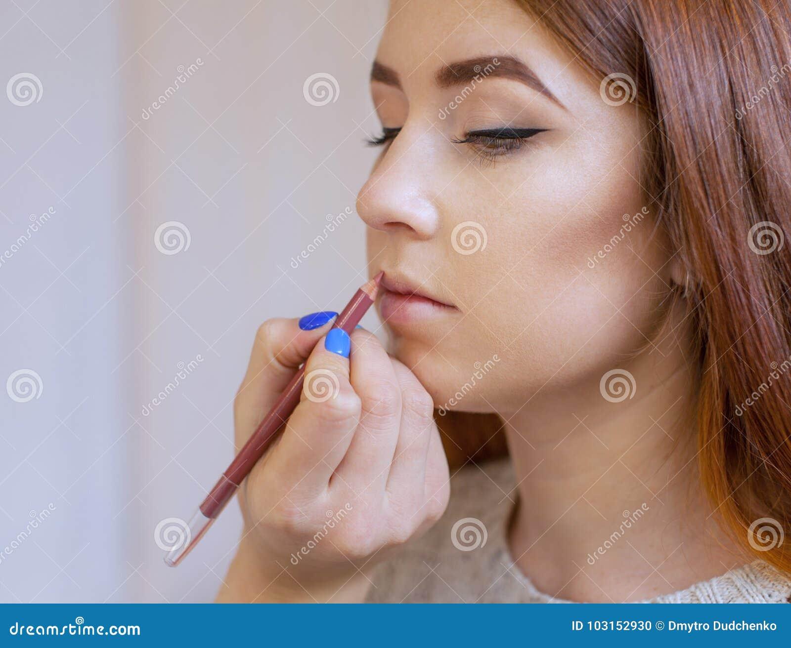 化妆师申请构成并且上色有一把专业刷子的唇膏在美容院