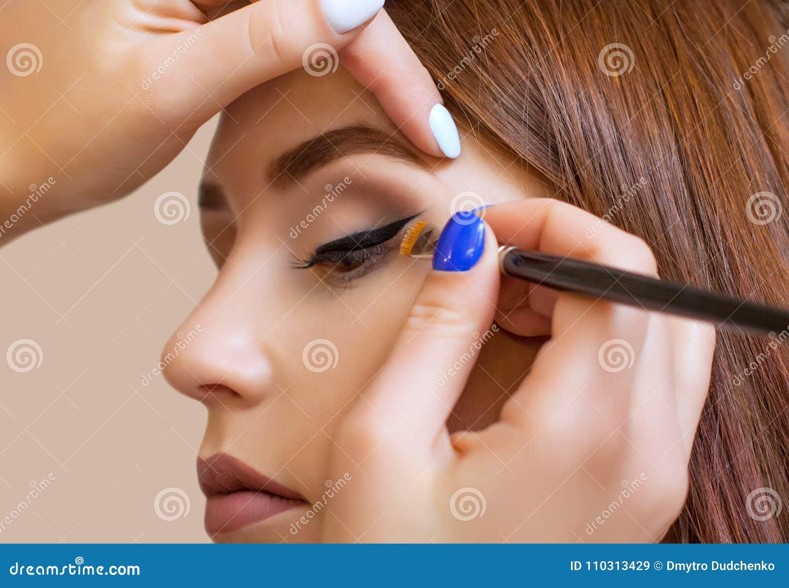 化妆师申请构成并且做与一把专业刷子的眼睛划线员在美容院