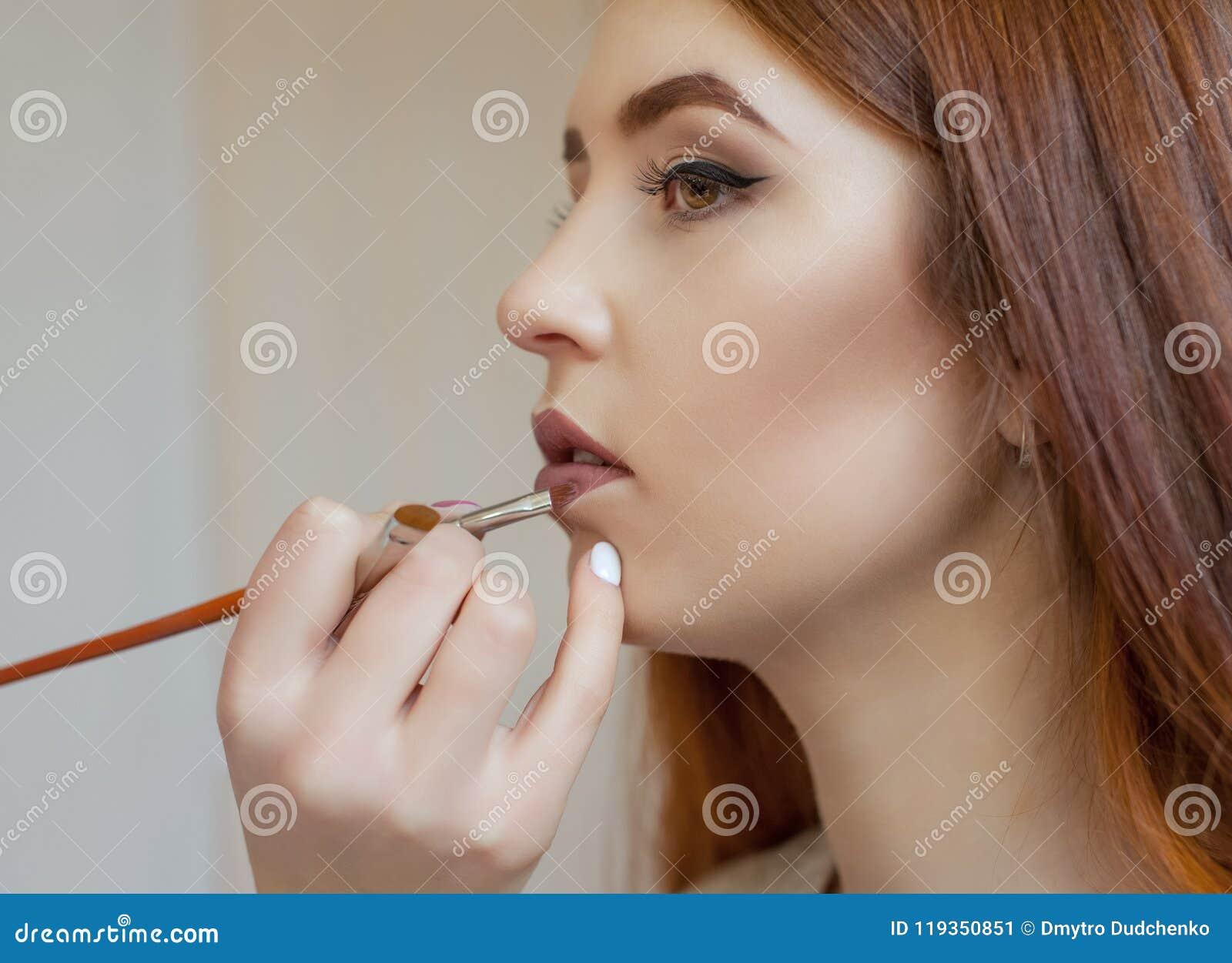 化妆师绘一个女孩的嘴唇有唇膏的在美容院