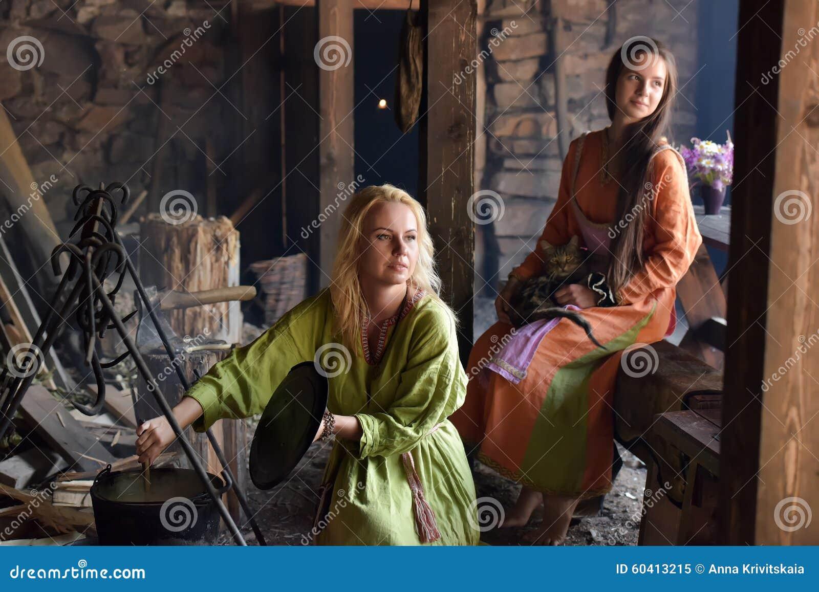 北欧海盗妇女准备在罐的食物在火