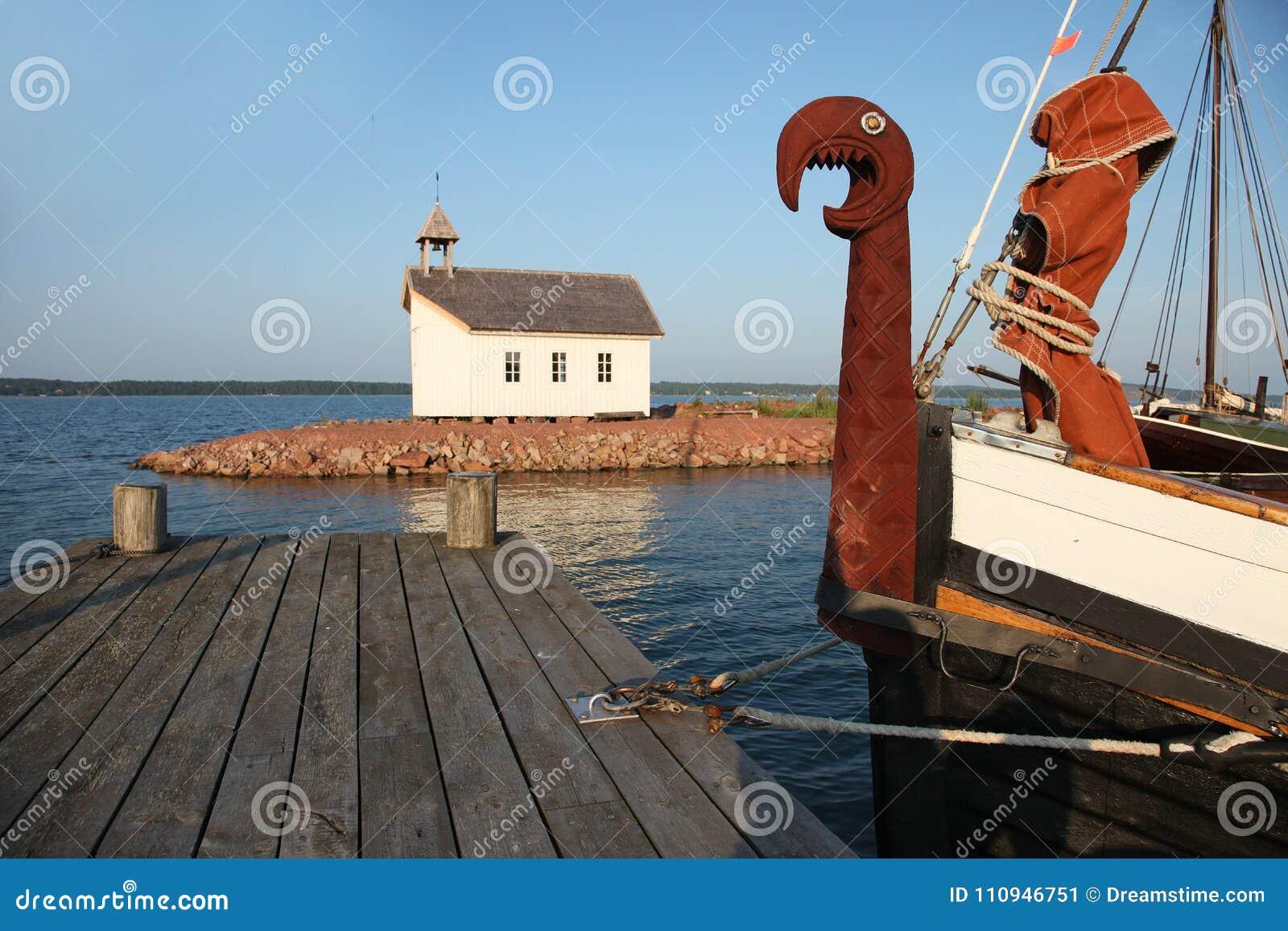 北欧海盗小船和教堂在造船厂在Marienhamn