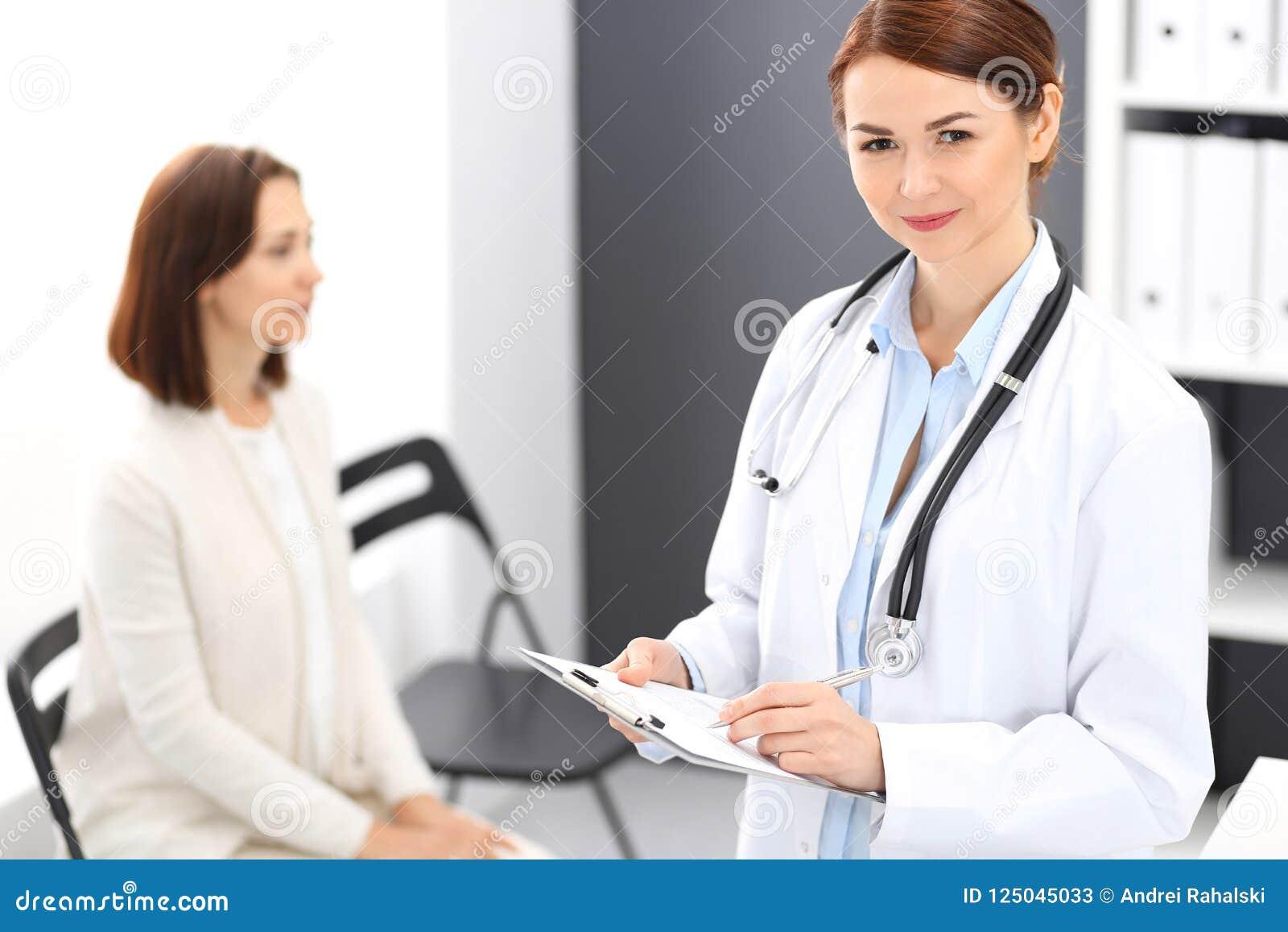 医生妇女在工作 填装医疗形式的女性医师画象,当站立近的总台在诊所时