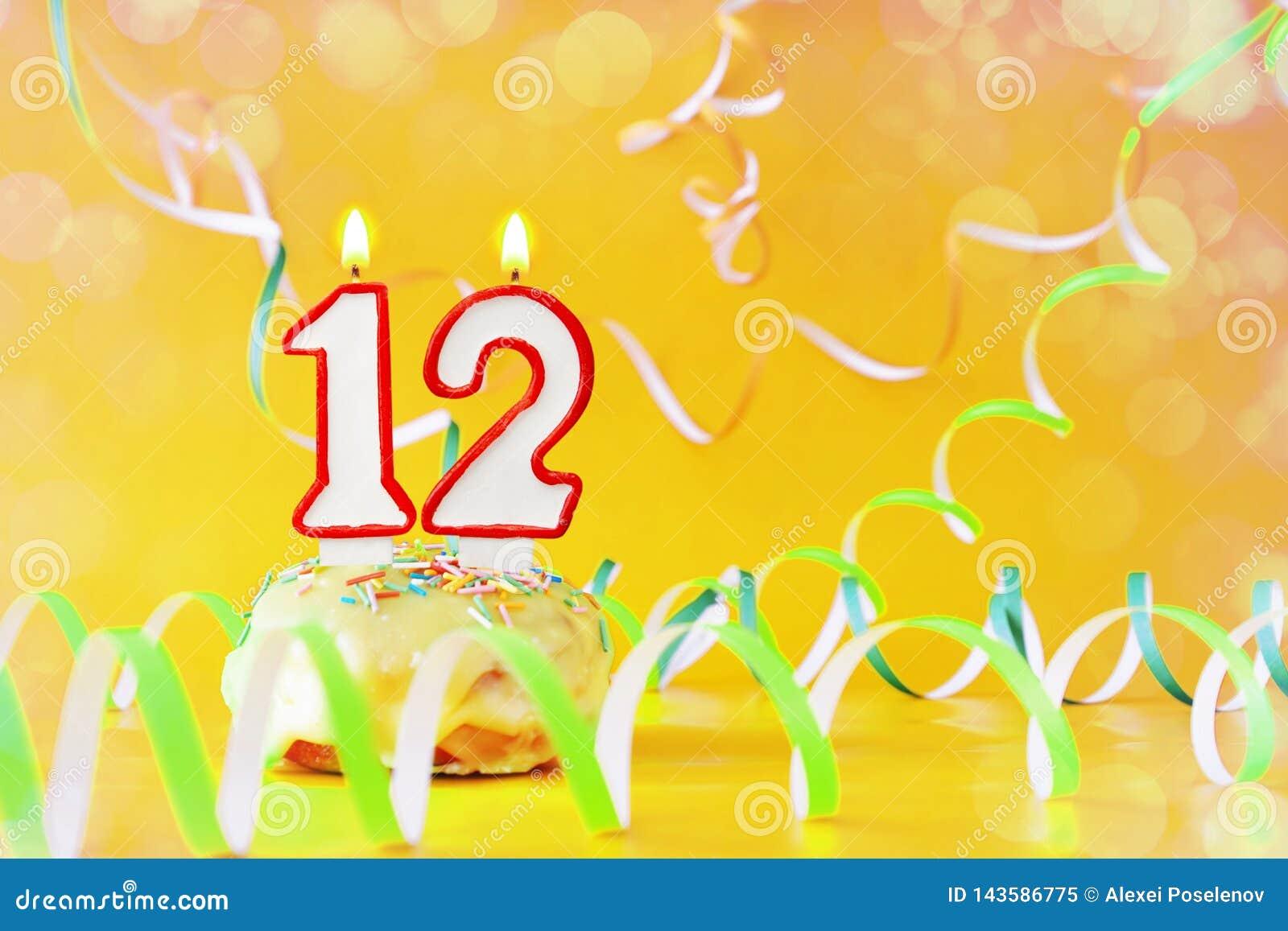 十二年生日 与灼烧的蜡烛的杯形蛋糕以第12的形式