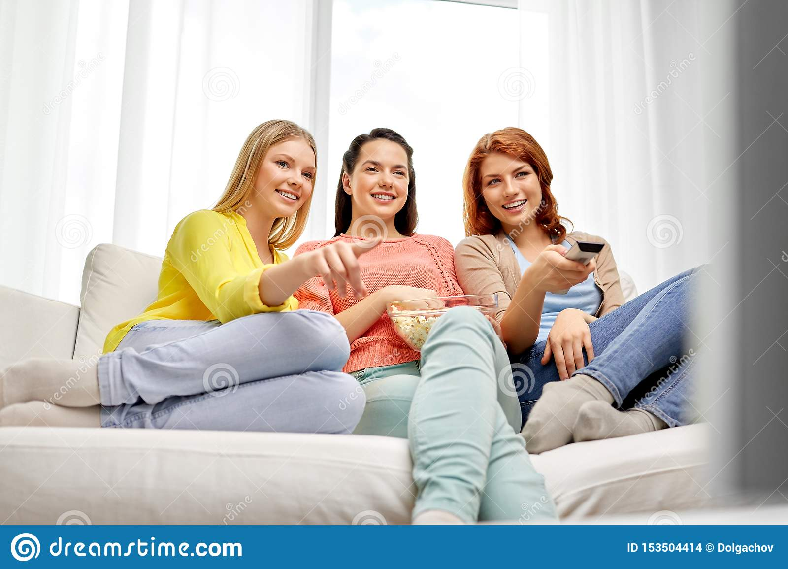 十几岁的女孩或朋友看着电视在家