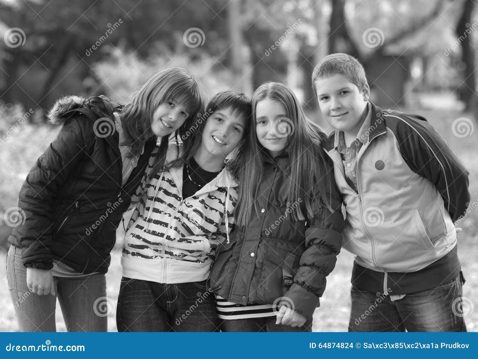 十几岁的男孩和女孩获得乐趣在公园在春天