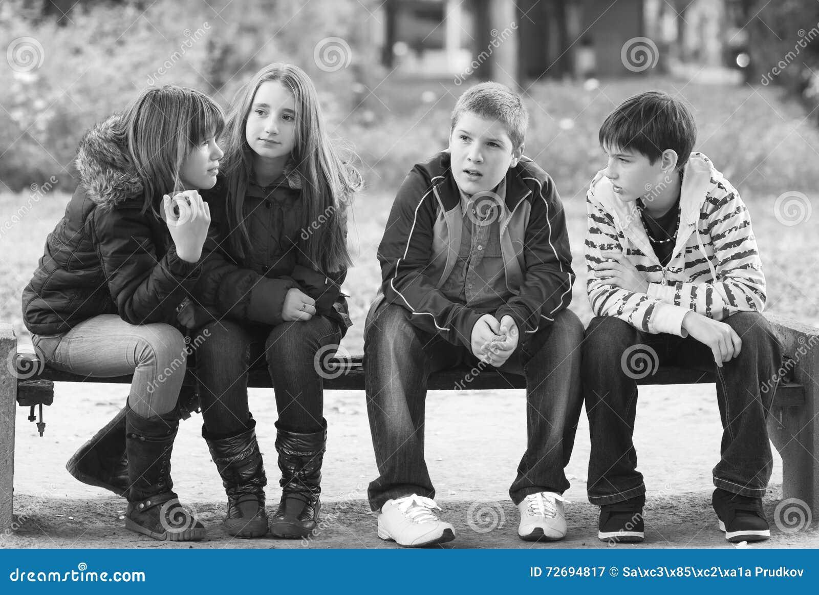 十几岁的男孩和女孩获得乐趣在秋天公园