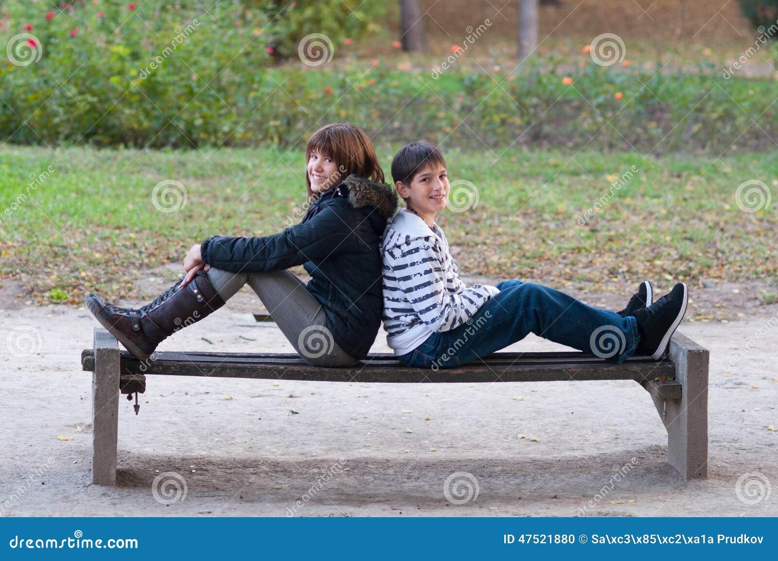 十几岁的男孩和女孩获得乐趣在美好的秋天的公园