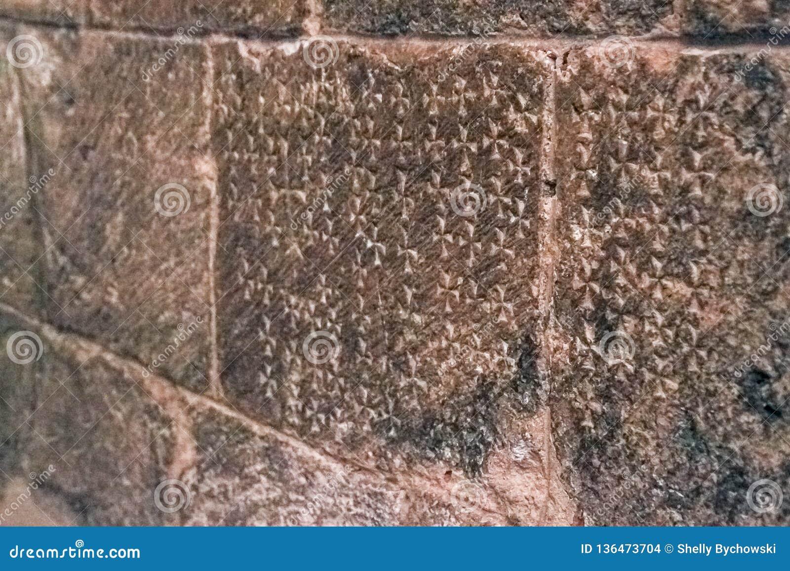 十字架被铭刻入圣洁坟墓的教会的石墙,表示耶稣的在十字架上钉死站点