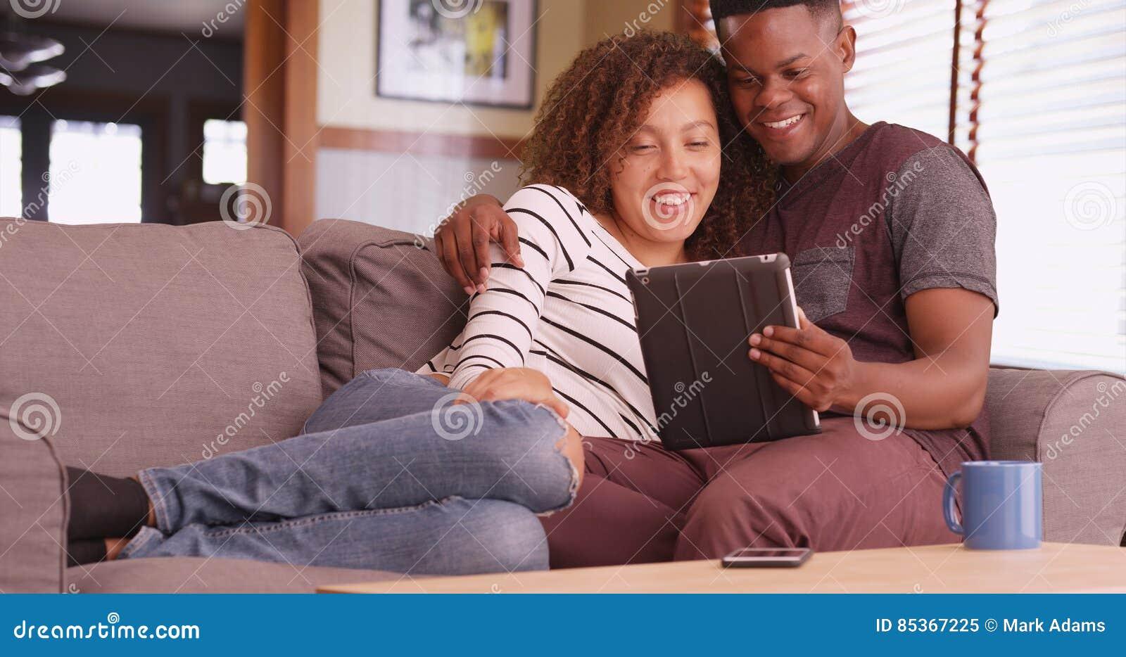 千福年的夫妇坐在他们的片剂计算机上的长沙发观看的电影