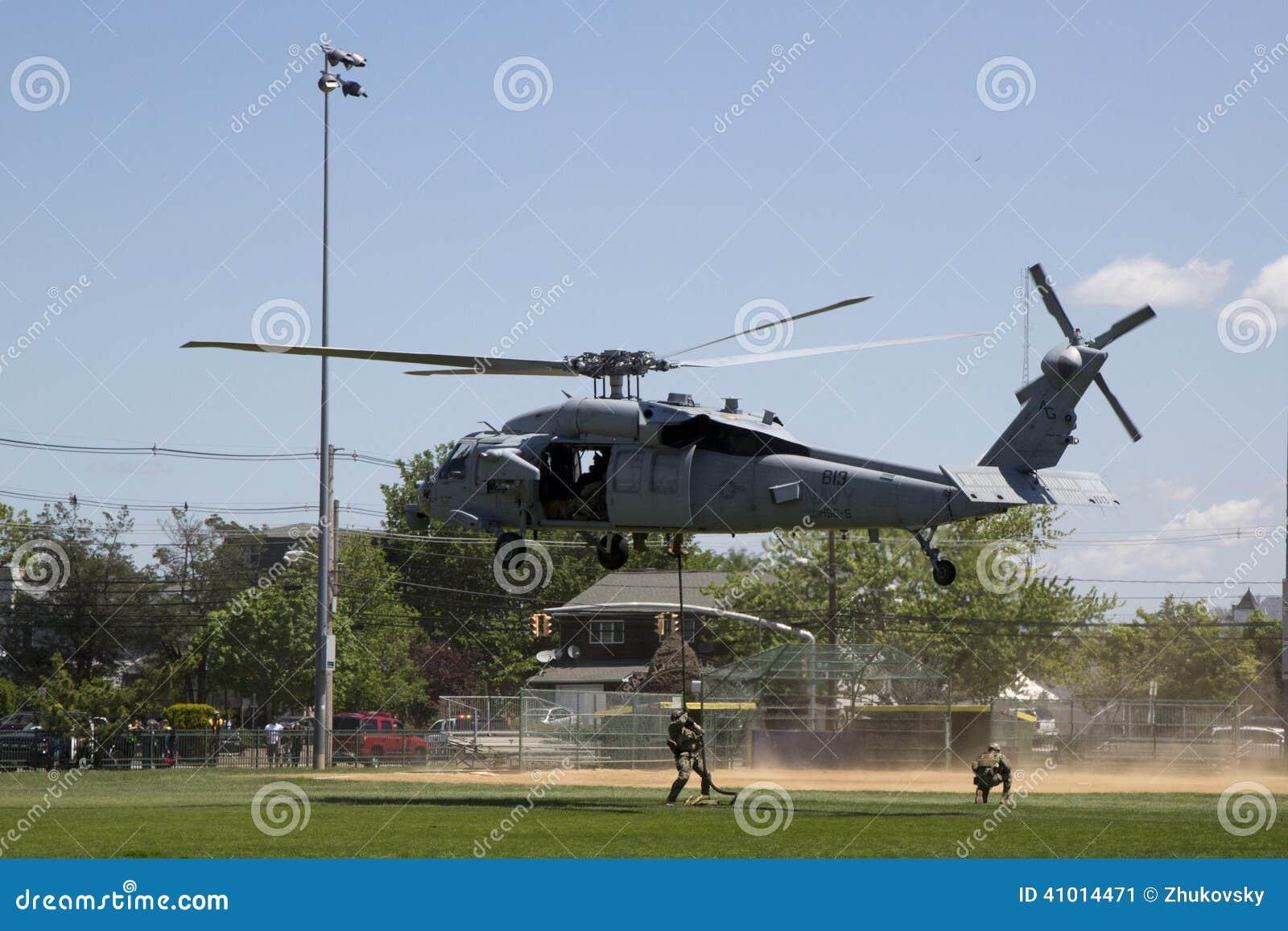 从直升机海的MH-60S直升机与与美国海军EOD队着陆的分谴舰队五交战水雷对抗措施示范的