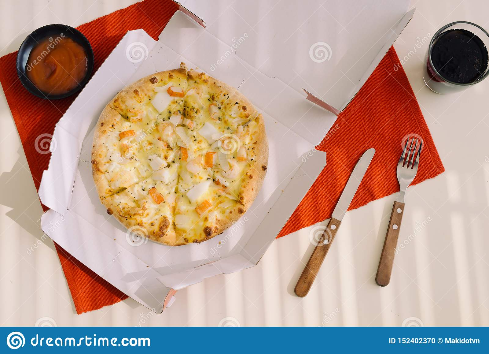 午饭时间,在一个开放箱子的比萨在桌上