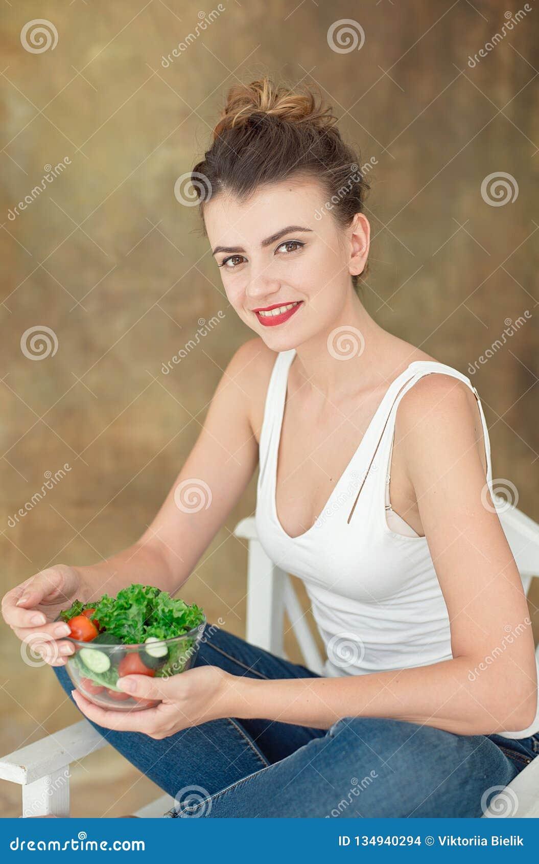 华美的健康妇女坐吃芝麻菜,有机蕃茄,在办公室期间的健康午餐的沙拉一把白色椅子