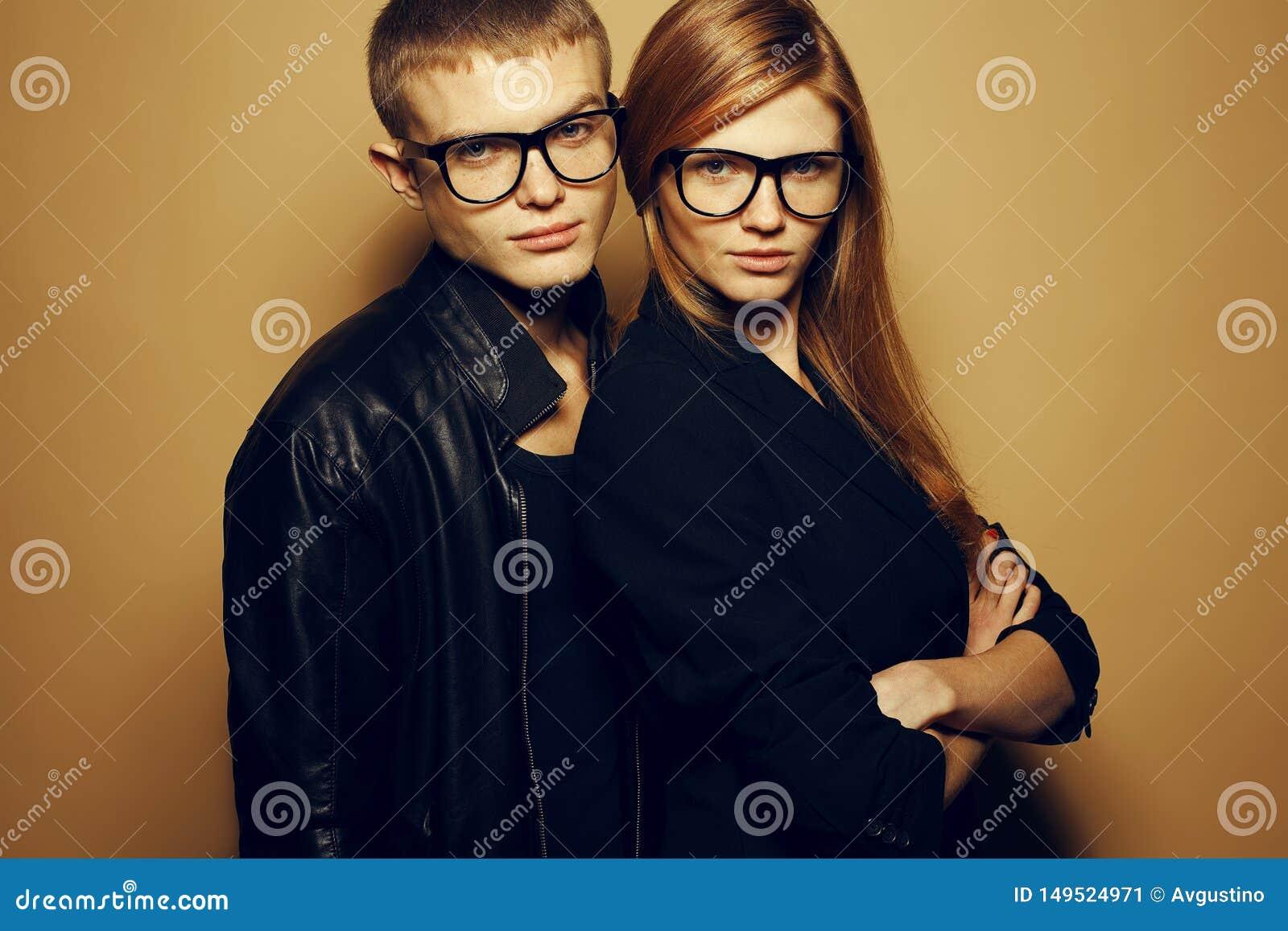 华美的红发时尚孪生画象在戴时髦眼镜和一起摆在米黄背景的黑色衣服的